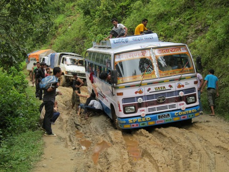 A bus stuck in the mud on the road to Arughat